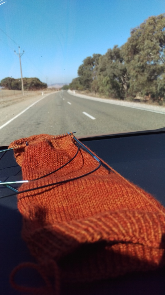 An orange sock in progress on the dashboard of a car, with a road and dry South Australian landscape and blue sky out of focus in the background.