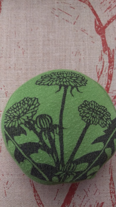 Small round green cushion with design of a dandelion in black