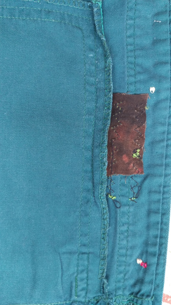 Patch on the inside of a green short beside front button band.
