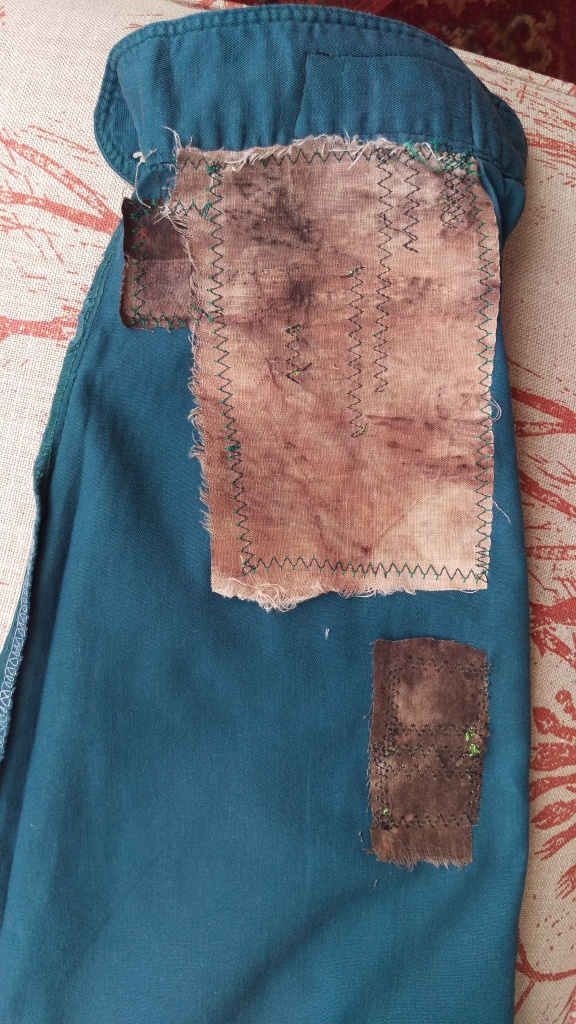 Inside view of a green short sleeve with eucalyptus printed fabrics stitched on as patches with machine zigzag.