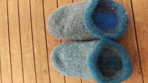 Blue felted slippers on a wooden plank background.