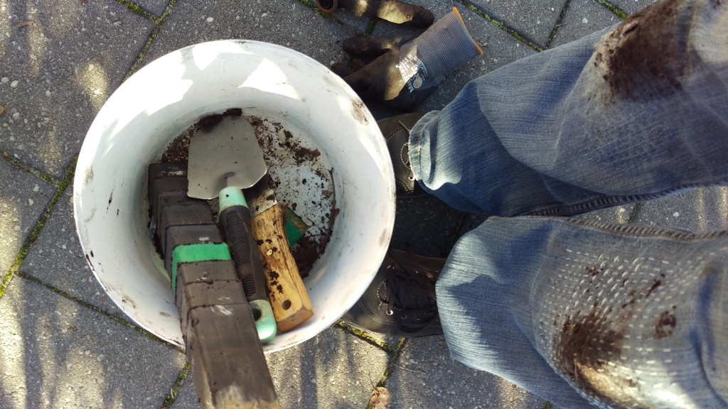 Muddy jeans, a bucket with empty pots and tools in it.